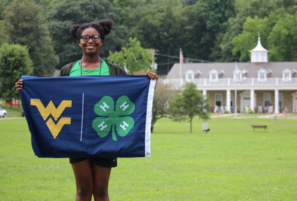 Girl holding a flag with a WV and 4H logo.